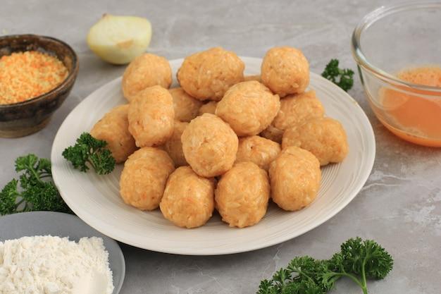 Arancini cru/boule de riz après la mise en forme ronde, étape avant d'enrober la chapelure de pentecôte ou la farine panko. préparation de la cuisson dans la cuisine