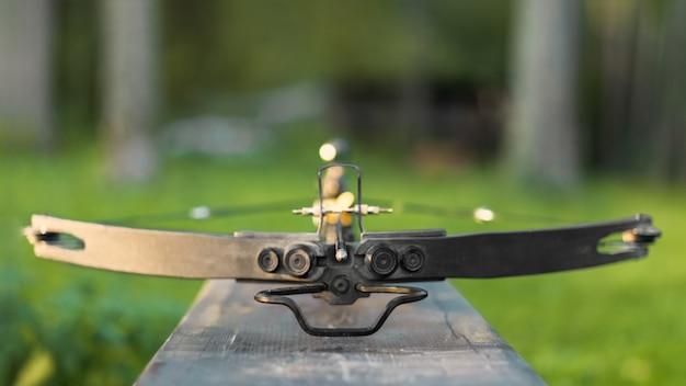 Arbalète chargée sur un banc en bois.