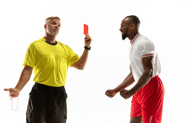 Arbitre montrant un carton rouge à un joueur de football ou de football afro-américain mécontent tout en jouant isolé sur un mur blanc. concept de sport, violation des règles, questions controversées, émotions.