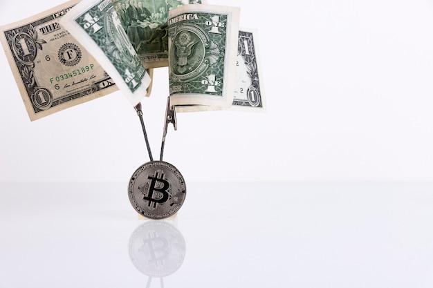 Arbre d'argent de billets d'un dollar et pièce de bitcoin isolé sur fond blanc. espace de copie.