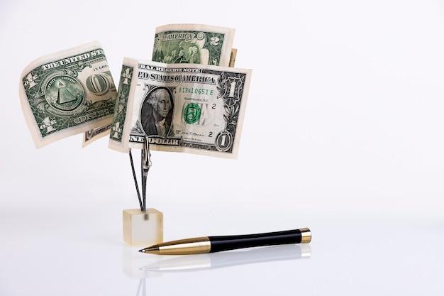 Arbre d'argent de billets d'un dollar et stylo d'affaires isolé sur fond blanc. espace de copie.