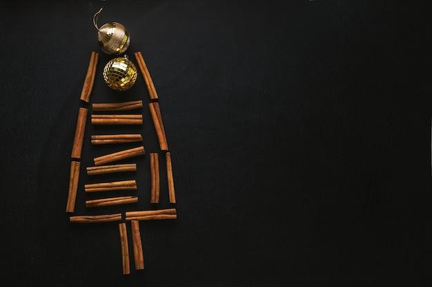 Arbre de noël abstrait avec des bâtons de cannelle et des flocons de neige sur fond sombre. concept de noël
