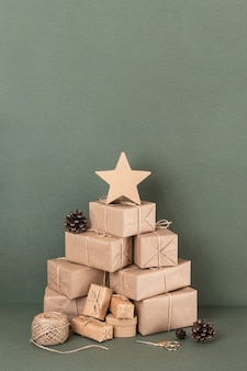 Arbre de noël abstrait. boîtes en papier kraft, ficelle, ciseaux, cônes sur fond vert, gros plan. concept vacances de noël ou du nouvel an. vue de face espace de copie.