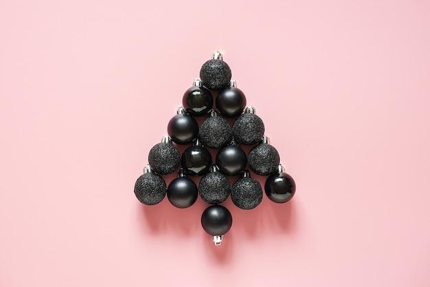 Arbre de noël abstrait fait de décoration de boules de boule noire sur fond rose