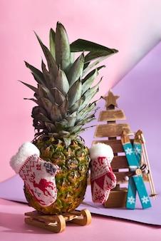 Arbre de noël d'ananas avec des mitaines d'hiver sur fond bicolore.