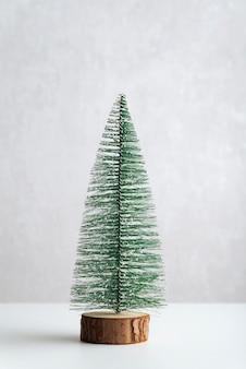 Arbre de noël artificiel miniature sur support en bois sur fond blanc. cadre vertical.