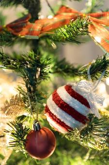 Arbre de noël assemblé avec des ornements. boules rouges, argentées et dorées, coffrets cadeaux, lumières, père noël et autres. mise au point sélective.