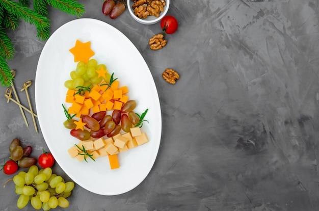 Arbre de noël au fromage avec raisins frais et romarin