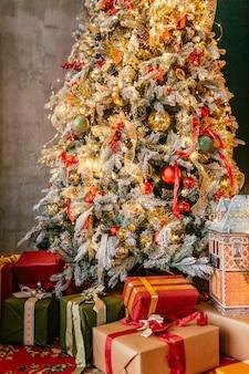 Arbre de noël aux couleurs vives dans une pièce avec tapis rouge avec beaucoup de cadeaux en dessous. vacances du nouvel an.