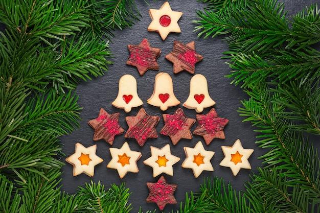 Arbre de noël de biscuits linzer faits maison avec confiture de framboises et étoiles de chocolat avec croquants de framboises sur table en ardoise avec des branches de pin