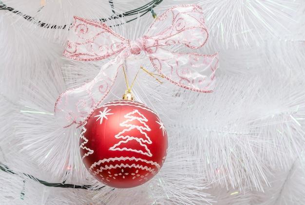Arbre de noël blanc avec une belle boule décorative avec un arc.