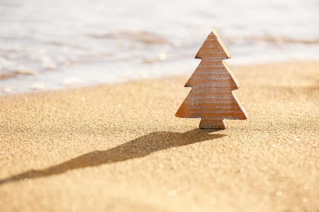 Arbre de noël en bois de bois sur un sable sur la plage tropicale près de l'océan