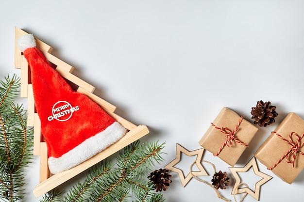 Arbre de noël en bois avec bonnet de noel à l'intérieur de coffrets cadeaux branches de sapin pommes de pin et étoiles en bois