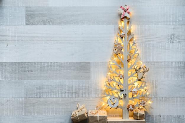 Arbre de noël en bois avec ornement de décoration naturelle et fond sur la vieille planche de bois