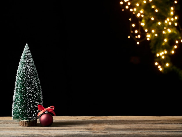 Arbre de noël et boules rouges sur table en bois contre les lumières de fête floues. espace pour le texte
