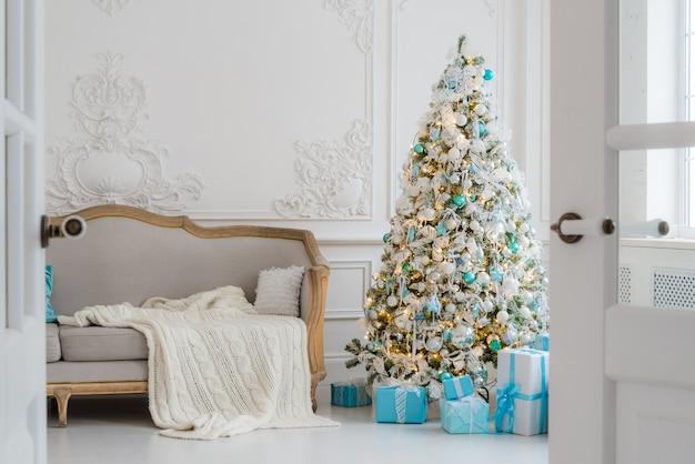 Arbre de noël avec des cadeaux cadeaux en dessous dans le salon
