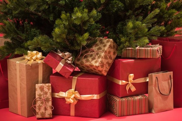 Arbre de noël avec des cadeaux sur fond rouge