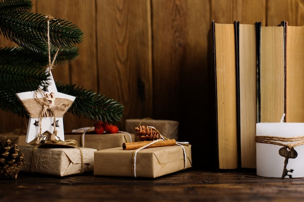 Arbre de noël, cadeaux, livres, étoile à la main sur une table en bois.