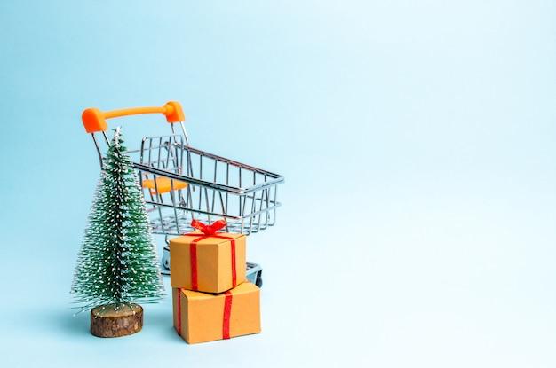 Arbre de noël, chariot de supermarché et cadeau sur fond bleu.