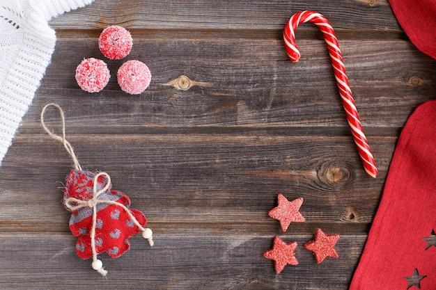 Arbre de noël avec des coeurs, de la canne à sucre, de minuscules pommes de sucre de neige, plaid en laine blanche et nappe rouge avec des étoiles sur une table en bois rustique