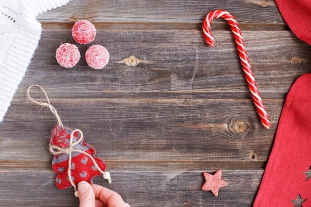 Arbre de noël avec des coeurs dans les doigts de la main, canne à sucre, minuscules pommes à sucre de neige, plaid en laine blanche et nappe rouge avec des étoiles sur une table en bois rustique