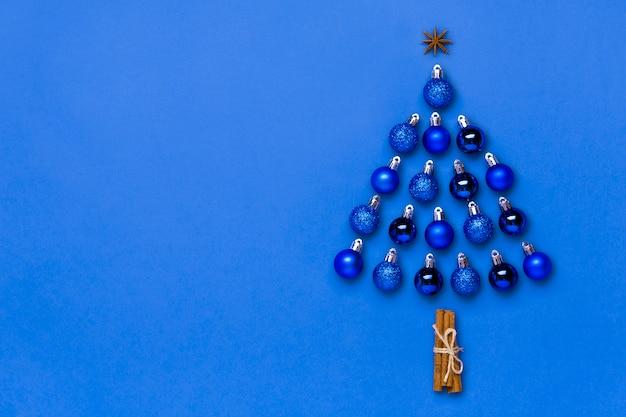 Arbre de noël créatif en boule bleue et décoration en étoile isolé sur la couleur de l'année 2020