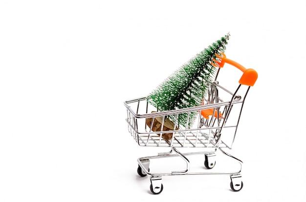 Arbre de noël dans un chariot de supermarché sur un fond blanc isolé.