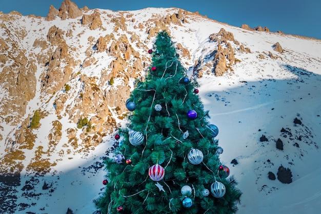 Arbre de noël dans la forêt de neige de montagne. arbre de noël décoré de grosses boules sur fond de montagnes.