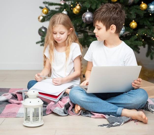 Arbre de noël dans un grand salon. les enfants jouent près du sapin de noël. un garçon avec un ordinateur portable communique avec des amis.