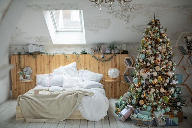 Arbre de noël dans une maison joliment décorée avec des cadeaux de noël en dessous.
