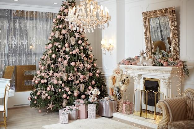 Arbre de noël debout intérieur du salon près de la cheminée boîte-cadeau se trouvent sur un tapis près de sapin à feuilles persistantes de noël. vacances du matin