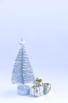 Arbre de noël décoratif et coffrets cadeaux sur fond de neige duveteuse.