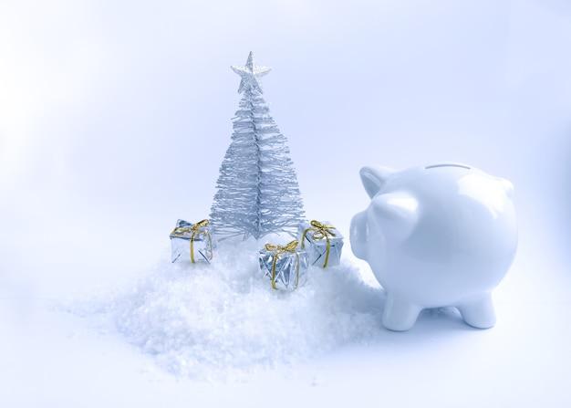 Arbre de noël décoratif, tirelire cochon en céramique blanche et coffrets cadeaux sur fond de neige duveteuse.
