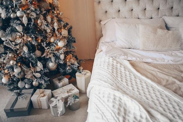 Arbre de noël décoré avec des cadeaux à l'intérieur de la chambre classique blanc