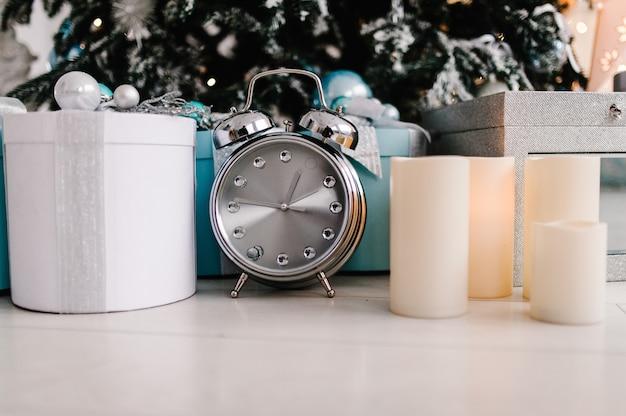 Arbre de noël décoré avec des coffrets cadeaux horloge bougies dans un décor de chambre blanche
