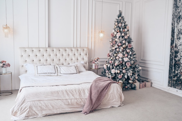 Arbre de noël décoré dans une chambre à coucher blanche classique avec bouquet de vacances du nouvel an dans un vase