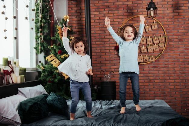 Arbre de noël derrière. enfants joyeux s'amusant et sautant sur le lit