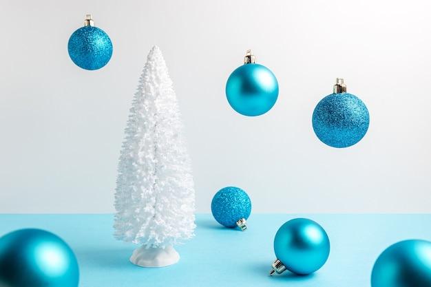 Arbre de noël enneigé avec décoration de noël sur table bleue