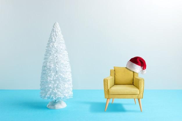 Arbre de noël enneigé avec fauteuil sur table bleue