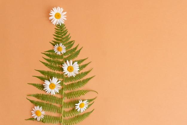Arbre de noël d'été fait de fleurs de fougère et de camomille avec espace de copie. célébration alternative du nouvel an