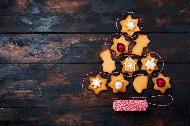Arbre de noël fabriqué à partir de biscuits en pain d'épice avec des jouets et un ruban rouge sur la vieille surface en bois. vue de dessus