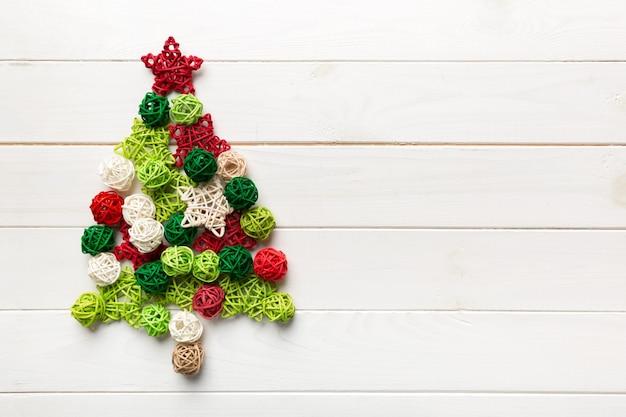 Arbre de noël fabriqué à partir d'une décoration de boule à la main colorée sur fond coloré, vue d'en haut. concept minimal du nouvel an avec espace de copie