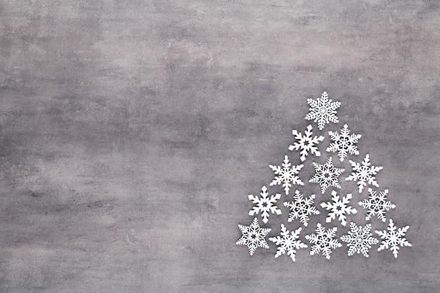 Arbre de noël fabriqué à partir de décorations de flocons de neige blancs sur fond gris avec un espace de copie vide pour le texte. carte postale de nouvel an et de noël.