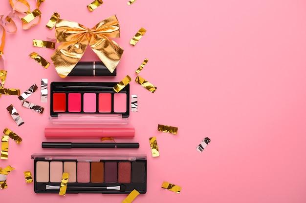 Arbre de noël fabriqué à partir de produits de maquillage sur une vue de dessus de fond rose. produits de beauté cosmétiques pour noël, rouge à lèvres, palette d'ombres, brillant à lèvres, eye-liner. cadeau de vacances concept pour une femme. espace de copie.