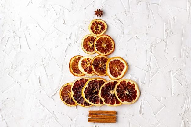 Arbre de noël fait d'agrumes séchés et de cannelle, anis sur fond blanc. oranges, citrons, pamplemousses en forme de sapin