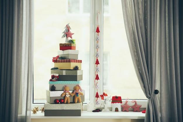 Arbre de noël fait de boîtes à cadeaux et autres décorations sur le rebord de la fenêtre