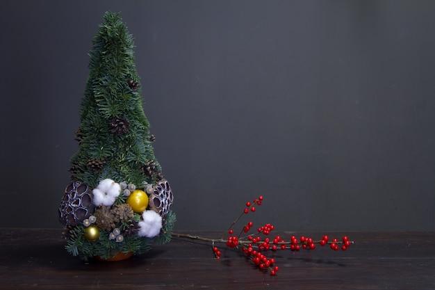 Arbre de noël fait de branches de sapin et décoré de matériaux naturels et d'une branche avec des baies de houx rouges