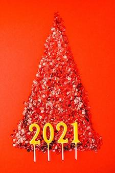 Arbre de noël fait de confettis brillants sur fond rouge. bougies en or de l'année 2021. carte de voeux de nouvel an et joyeux noël. concept de vacances