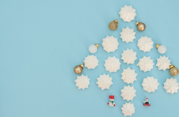 Arbre de noël fait de meringues blanches avec des boules de noël dorées et blanches et des décorations de noël en bois sur fond bleu clair