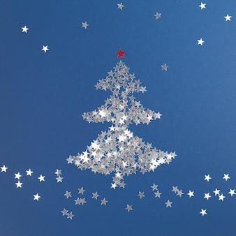 Arbre de noël fait de paillettes d'argent en forme d'étoiles composition de noël nouvel an blue backgrou